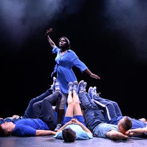 Eine Gruppe Tänzer liegt auf dem Boden und streckt die Füße in die Luft. Eine Tänzerin in einem blauen Kleid steht in der Mitte und hebt einen Arm in die Höhe.