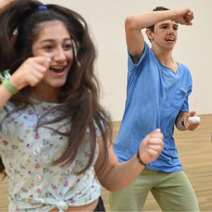 Ein Junge und ein Mädchen tanzen in einem Trainingsraum.